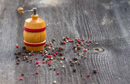 Multicolored peppers peas and pepper mill on wooden table