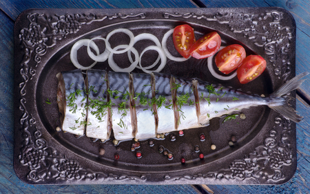 Salted mackerel with vegetables on the plate on a wooden table, top view