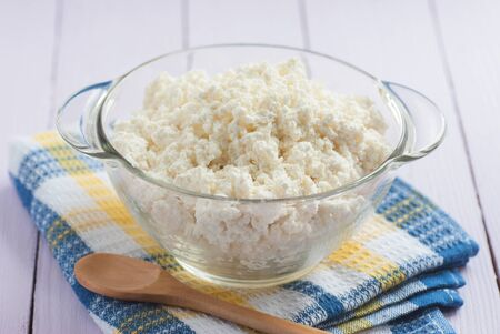 Fresh cottage cheese in a glass with a wooden spoon, close-up, selective focus