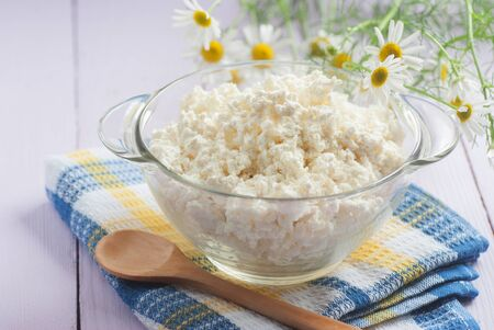 Cottage cheese in a glass container, a wooden spoon and chamomile flowers, close-up, selective focus Stock Photo