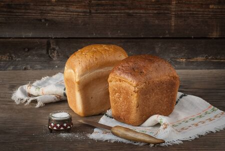 Two fresh loaves of bread, knife, salt lying on a wooden surface Stock Photo