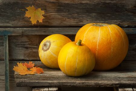 Three ripe pumpkins and maple leaves on a wooden table
