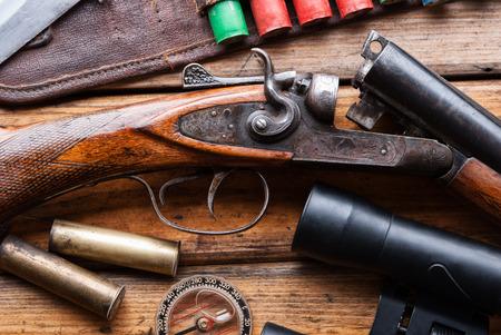 The hunting rifle, cartridge belt,binoculars,ammunition on a wooden table