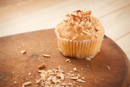 Cake in white glaze with chopped almonds on a wooden table,selective focus