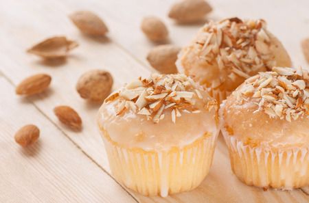 Cakes in white glaze with almonds on a wooden table