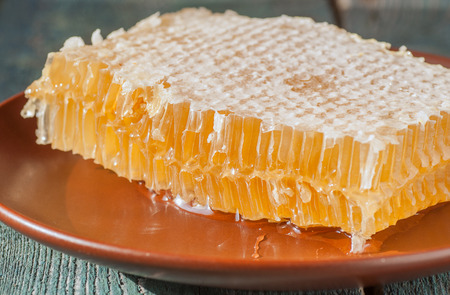 Fresh honeycombs on a wooden table closeup, selective focus Stock Photo