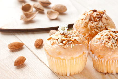 Cupcakes in white glaze with almonds on a wooden table Stock Photo