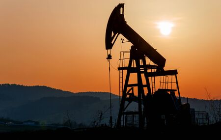 dug well: Oil rocking silhouette against a background sunset Stock Photo