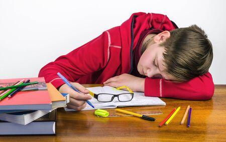 exemplary: sleeping student performs homework Stock Photo