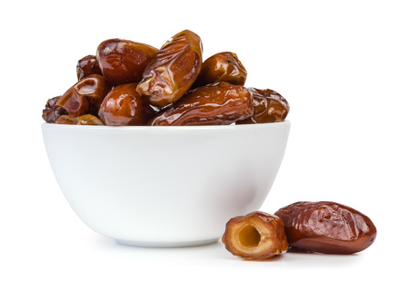 deglet: Dried dates fruit in a bowl, isolated on a white background