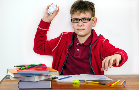 impish: rowdy schoolboy sitting at a school desk Stock Photo