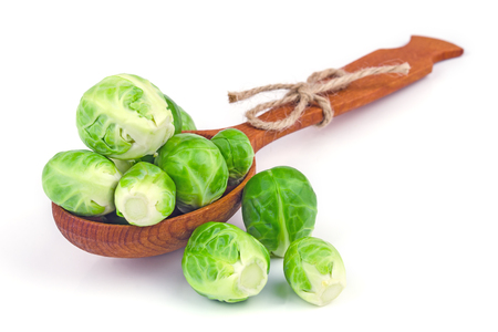Brussels sprouts imposed on a wooden spoon on a white background