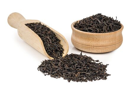theine: Black loose tea with a wooden shovel isolated on white background Stock Photo