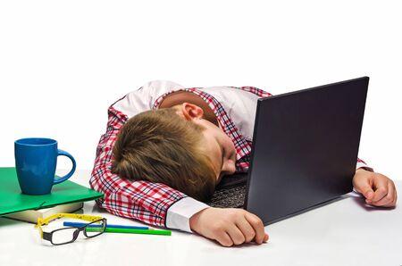 exemplary: boy fell asleep at the computer keyboard Stock Photo