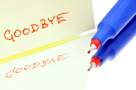 terminating: Hand written word  goodbye  on paper laid on the glass with a pencil  Stock Photo