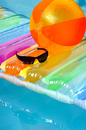Airbed,ball,and sunglasses in the pool