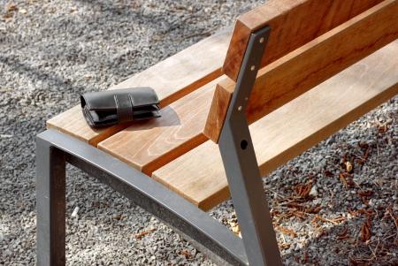 Negro mens billetera tirada al aire libre en un banco de madera Foto de archivo - 22498080