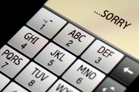 SMS text messages  SORRY  written on a touch screen phone