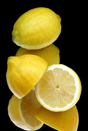 shoppe: Lemons lying on mirror glass  Stock Photo