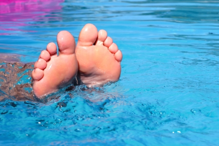holidays vacancy: Women feet in the water in the pool  Stock Photo