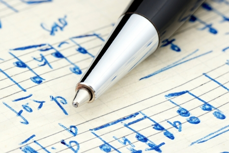 Handwritten notation on which is lying pen