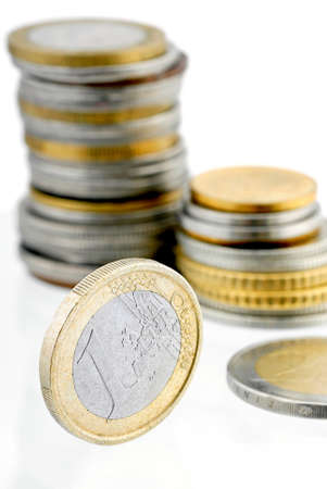 economise: Currency euro coins with a background of various metal coins  Stock Photo