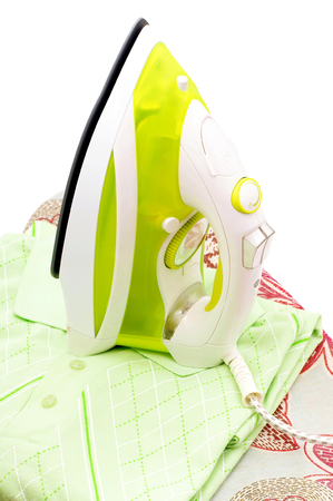 Electric iron standing on a shirt and ironing board  photo
