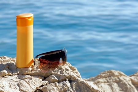 holidays vacancy: Sunscreen and sunglasses on a rock by the water