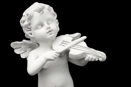 Statuette of an angel who plays the violin on black background  photo