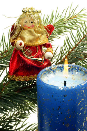 angelical: Christmas ornament on a branch firs in the foreground lit candle