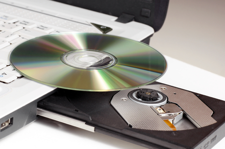 transferable: CD DVD disc lying on a laptop with a protruding drive  Stock Photo