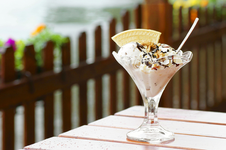 Ice cream with chocolate and nuts on the table in the rainy weather Stock fotó