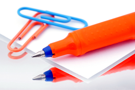 Writing pen on the paper which lies next to a paperclip  Stok Fotoğraf