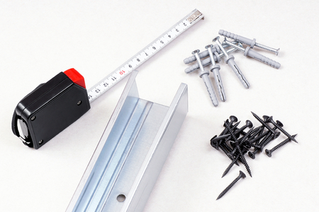 Preparation for installation of gypsum board- metal profiles, screws, dowels knock a tape measure  Stock Photo