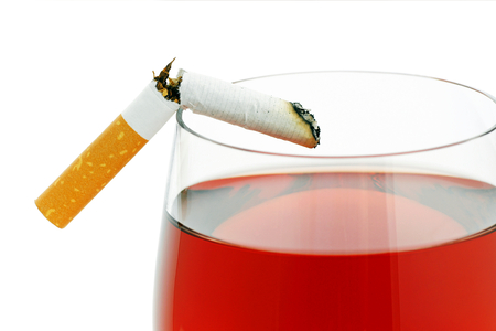 Broken cigarette on a glass of wine.