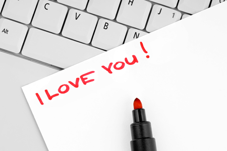 Paper with handwritten sentence I love you on a laptop keyboard. photo