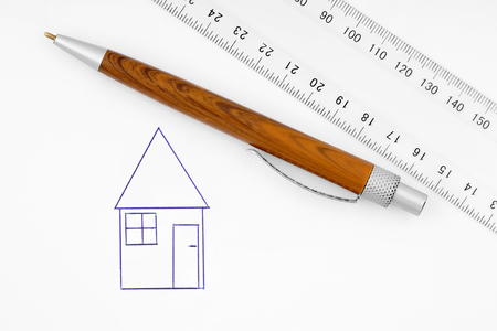 millimetres: Ballpoint pen,ruler lying on the paper on which it is drawn house. Stock Photo