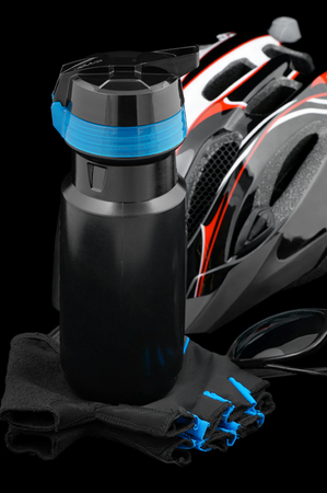synthetically: Cycling needs-bottle,glove,sunglasses,and helmet on a black background.