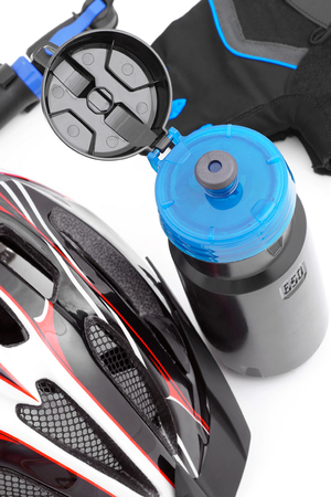 Cycling accessoriesbottle,helmet,gloves and bicycle pumplying side by side on a white background.