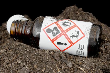 riesgo quimico: Botella con residuos peligrosos tirado en el suelo. Foto de archivo