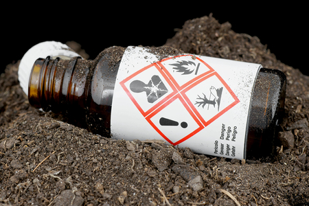 cautionary: Bottle with hazardous waste thrown in the ground. Stock Photo