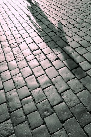 dangerously: Shadow of a figure on the city pavement.