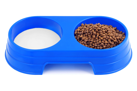 granules: Cat food in a double bowl meat granules and milk.
