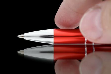 ボールペンに手を伸ばし指。