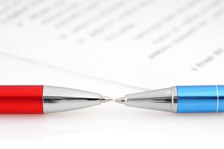 ball pens stationery: Dos plumas son opuestas entre s� con el fondo del documento.