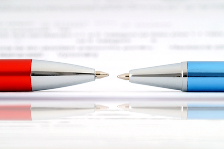 Two ballpoint pens lying against Each Other and document. Stock Photo