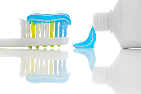placed: Toothbrush and toothpaste Placed on a glossy surface.