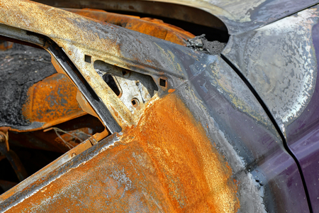 A close shot of the burned and rusty door of a passenger car.