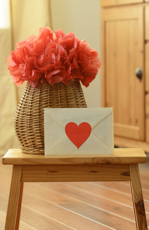 Vase basket with red tissue paper flower-pom pom, and envelope with red heart shaped sticker on the small wooden step stool photo