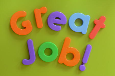 great: Close up of Great Job  words in colorful plastic letters on green background Stock Photo